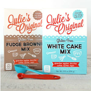 Julie's Original Gluten-Free and vegan Fudge Brownie and White Cake mix boxes with measuring spoons
