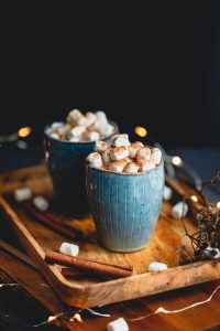 Hot chocolate with marshmallows and cinnamon in blue ceramic cups on a table.